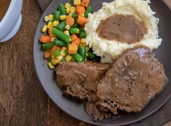Round Steak with Mashed Potatoes and Gravy ready to be served on a gray plate
