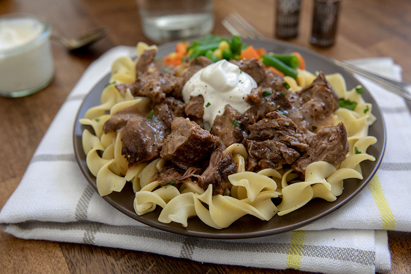 A plate of pasta topped with round steak in gravy and a dollop of sour cream.