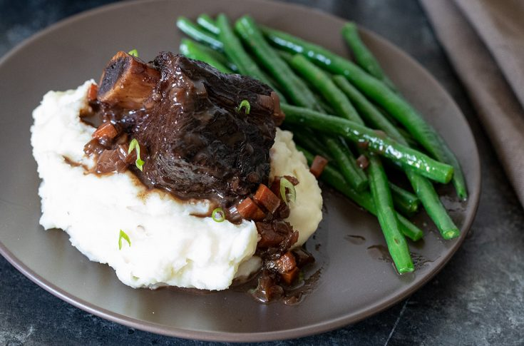 closeup of braised beef short ribs on a plate with mashed potatoes and green beans