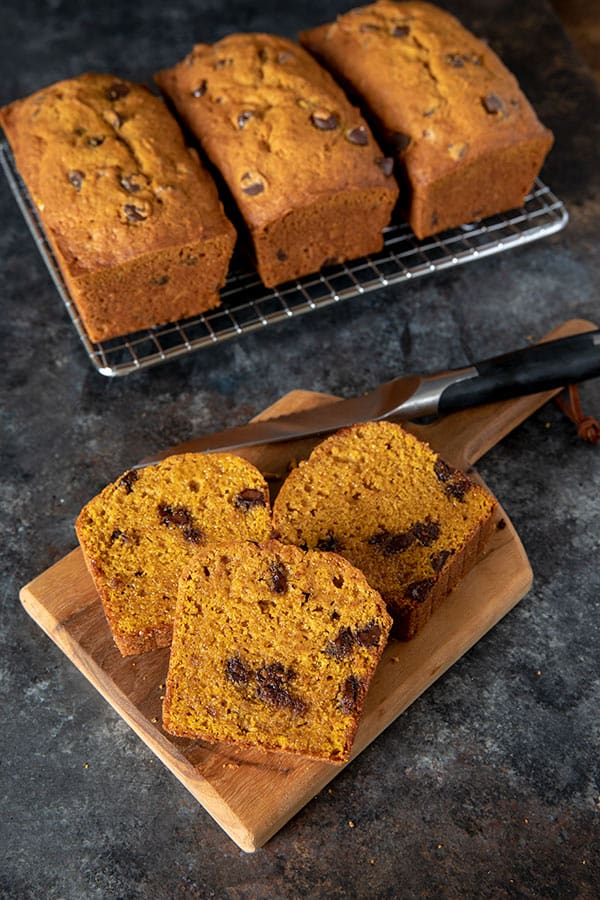 Pumpkin Chocolate Chip Bread slices on a wooden cutting board with a sharp bread knife