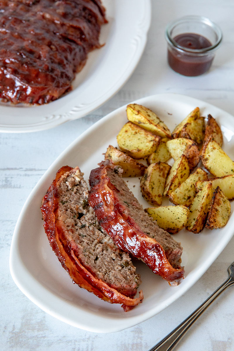 BBQ Bacon Pioneer Woman Meatloaf on a tray with roasted potatoes