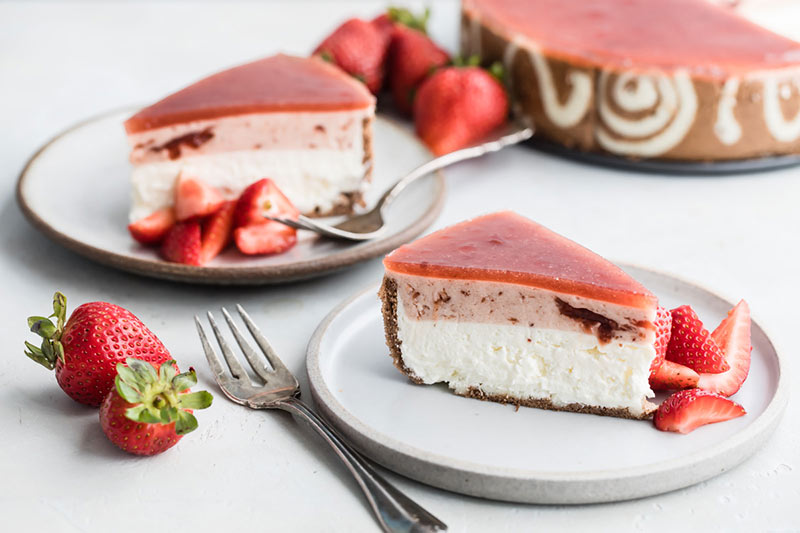 a slice of strawberry-lemon-cheesecake-entremet on a white plate with a fork
