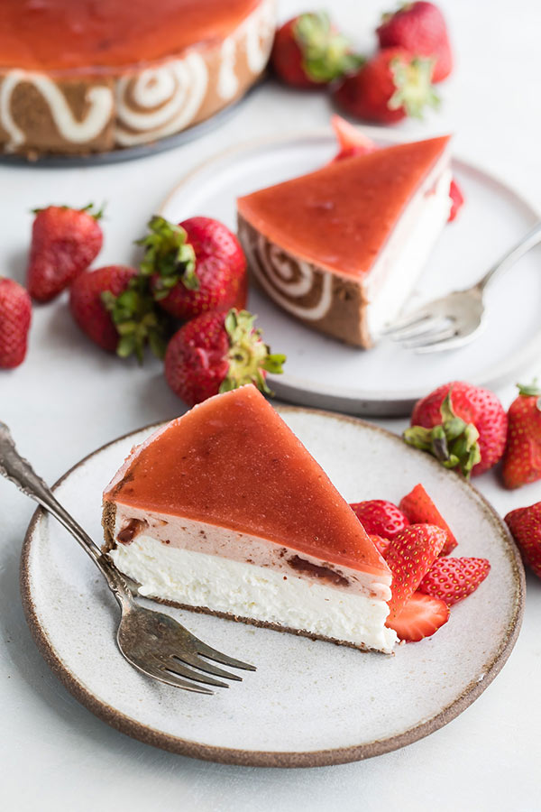 strawberry-lemon-cheesecake-entremet-slices on two white plates with forks