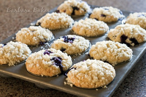 a muffin tin with 12 blueberry muffins topped with struesel