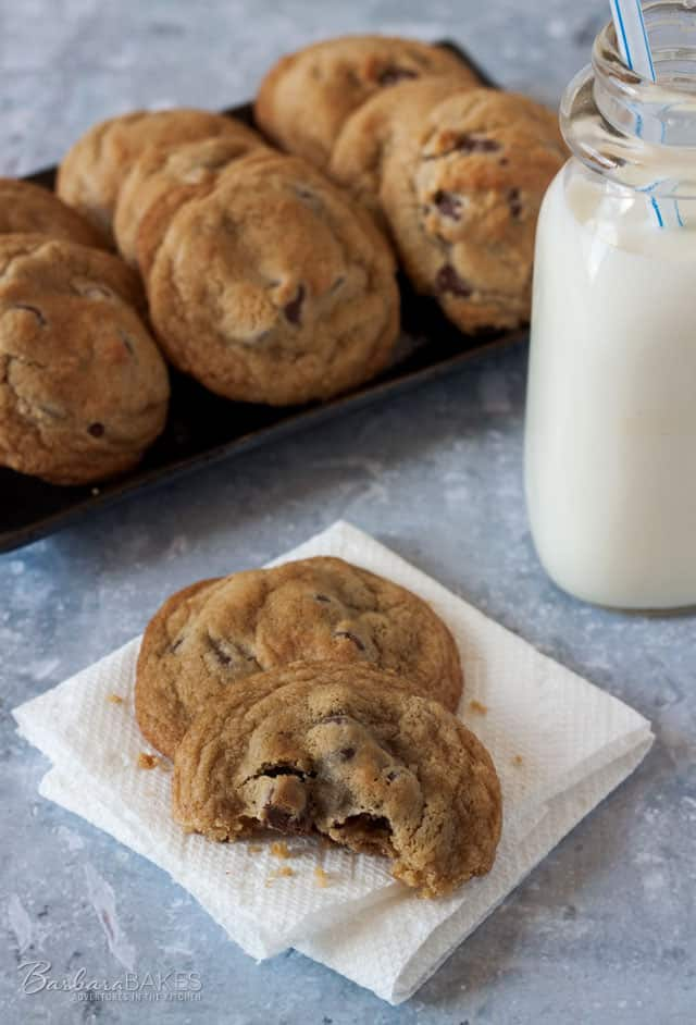 Thick, Chewy Chocolate Chip Cookies on a platter with a mini jug of milk.