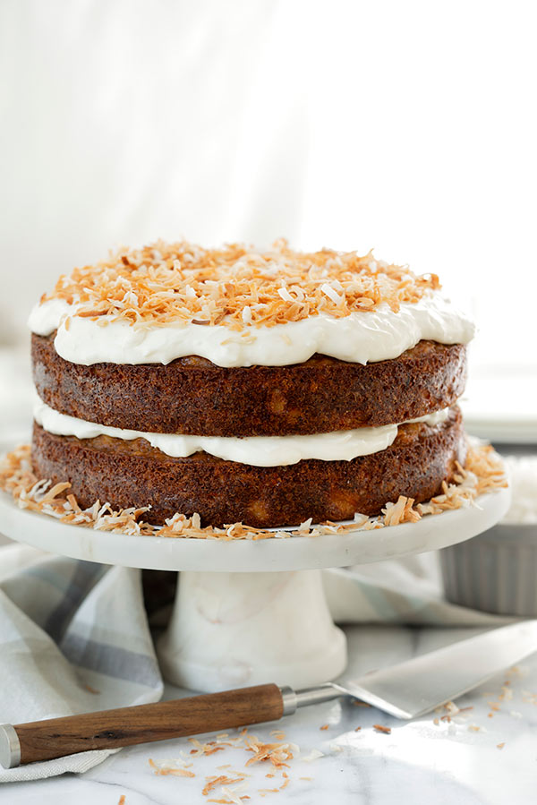Two layer Tropical Carrot Cake with Toasted Coconut Cream Cheese frosting on a cake stand
