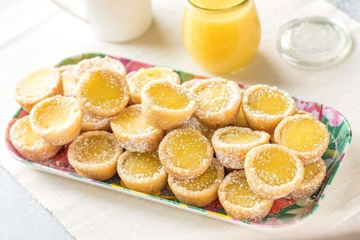 A serving dish full of several bright yellow lemon bar cookie cups