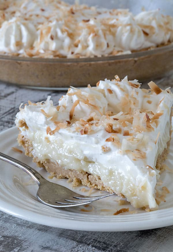 A slice of Coconut Cream Pie in a Shortbread Crumb Crust served on a white plate with a fork