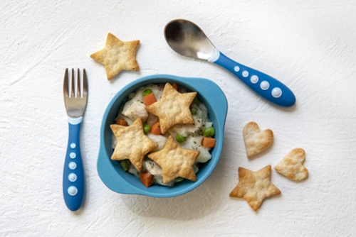Deconstructed Chicken Pot Pie in a child\'s blue bowl with children\'s fork and spook