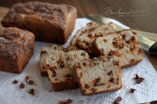 sliced snickerdoodle bread with cinnamon chips backed by two uncut loaves