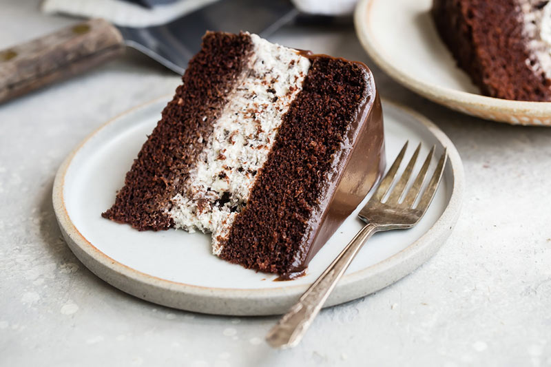 A slice of chocolate cake with an Oreo Cheesecake Filling on a plate with a fork.