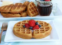 Completed whole wheat waffle recipe served on a plate with fruit and a dusting of powdered sugar.