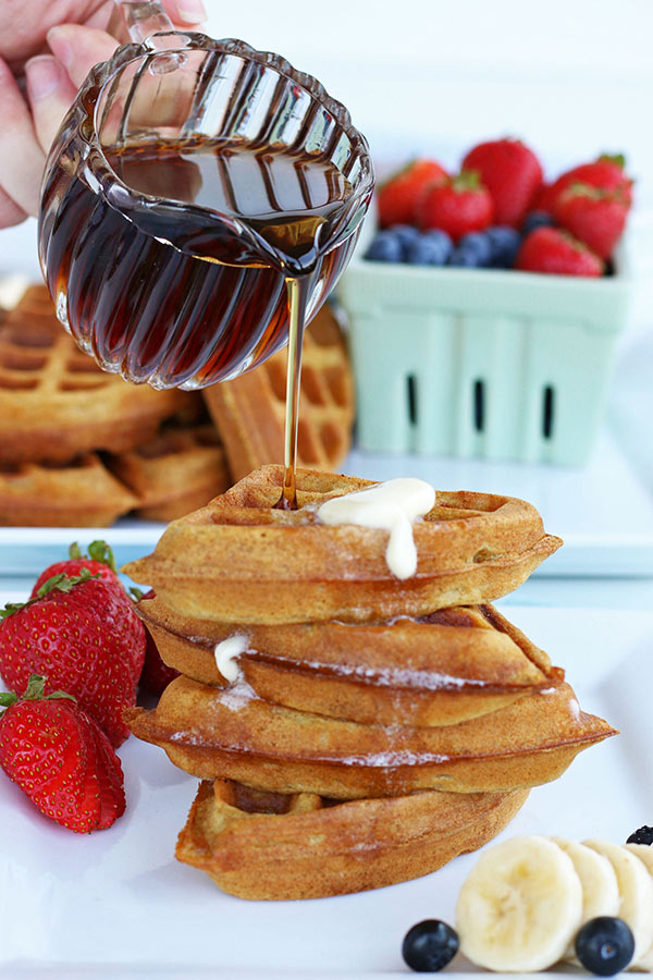 Syrup being poured onto a stack of whole wheat waffles in quarters on a plate ready to eat.