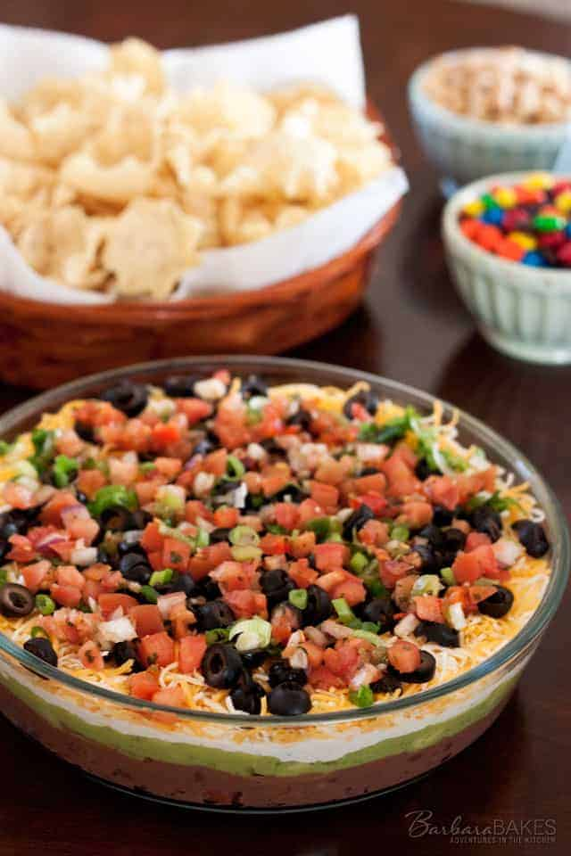 A classic 7 layer bean dip made by layering refried beans, creamy guacamole, spicy sour cream, cheese, olives, green onions, and fresh salsa.