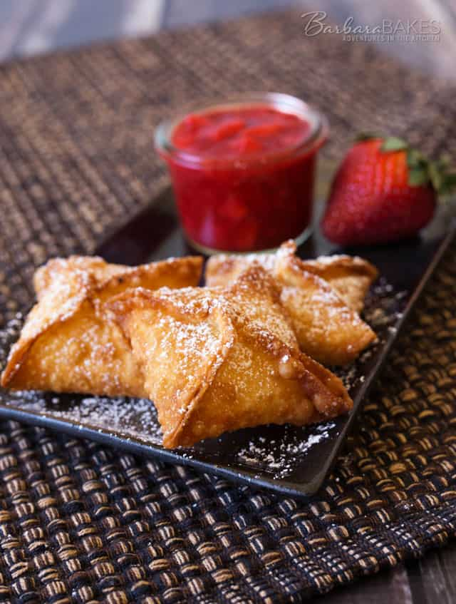 Strawberry Cheesecake Wontons with a cheesecake filling deep fried until they're golden brown and crispy, then served with a sweet, fresh strawberry sauce.