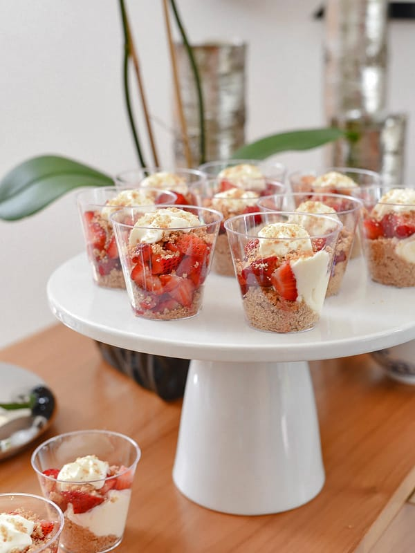 Strawberry Cheesecake in a Jar shown on a white cake stand