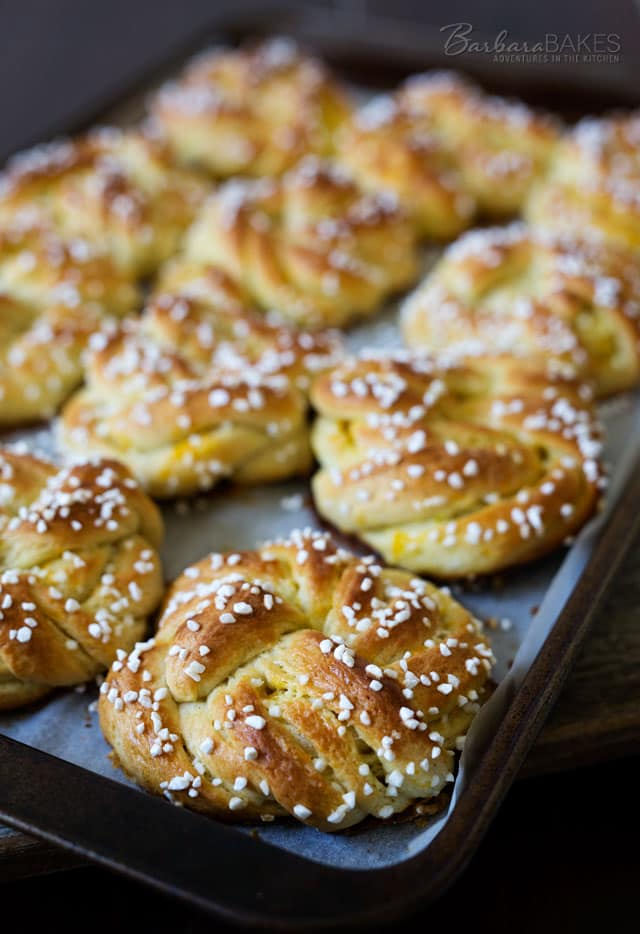 Swedish Orange Sweet Buns made with a buttery, cardamom dough layered with fragrant orange sugar, then knotted, topped with Swedish pearl sugar and baked until they\'re golden brown.