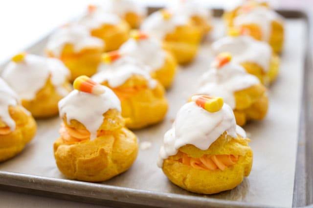 These fun Candy Corn Cream Puffs start with a bright yellow cream puff shell which is filled with an orange cream cheese filling, iced with a bright white icing, and finished with a candy corn on top.
