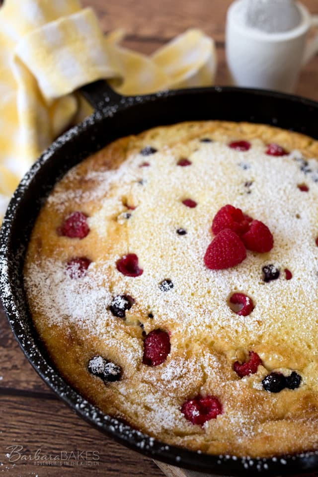 A rich, custardy Lemon Ricotta Dutch Baby Pancake studded with blueberries and raspberries and served with a sprinkle of powdered sugar.