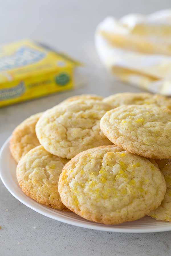 Lemon Doodle Cookies stacked on a plate after being rolled in yellow sugar and crushed Lemonhead candies.