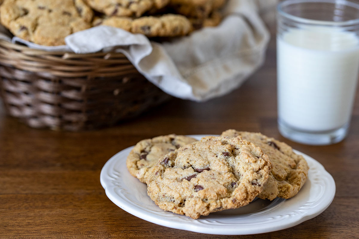 Three chocolate chip cookies on a plate with a glass of milk and a basket of cookies in the background