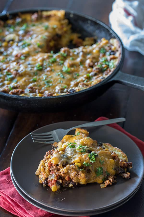 a tamale pie skillet dinner and a slice of the pie on a dinner plate in front of it