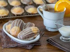 Glazed Chocolate Orange Marbled Madeleines on a white plate with a cup of tea