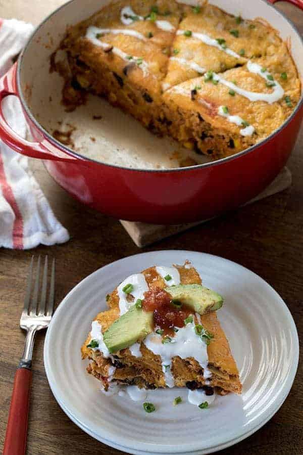 easy breakfast casserole made with chorizo, corn and black beans. A serving of the casserole is on a plate in front of the casserole dish