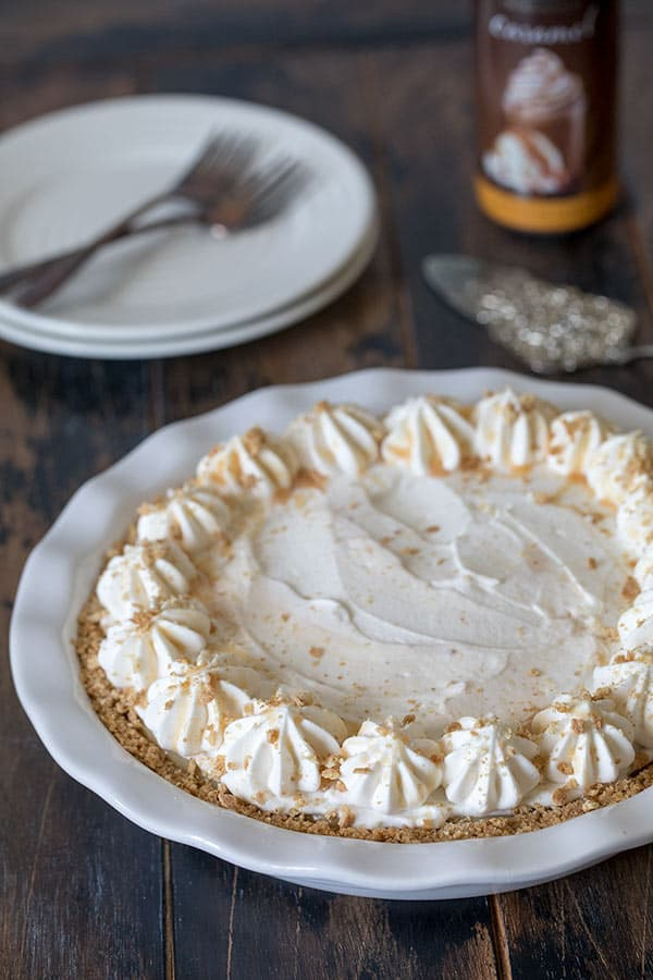 Brown Sugar Banana Cream Pie decorated with graham cracker crumbs and caramel.