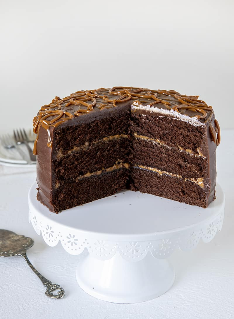 Triple Layer Chocolate Dulce De Leche Cake with a large slice taken out of it on a white cake stand