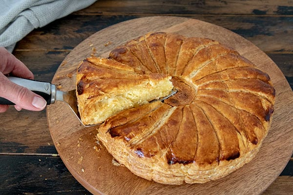 Sliced Pithivier pastry on a wooden platter