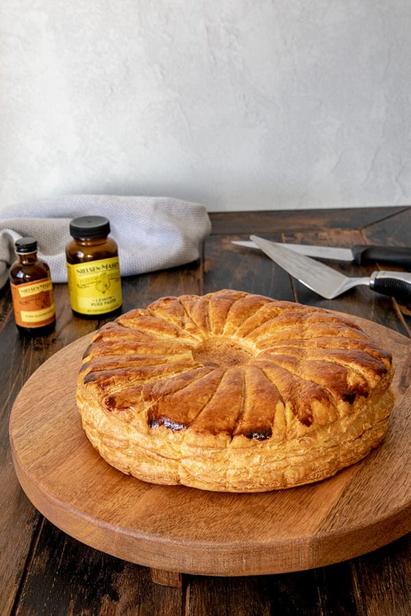 Golden brown Pithivier pastry on a wooden platter