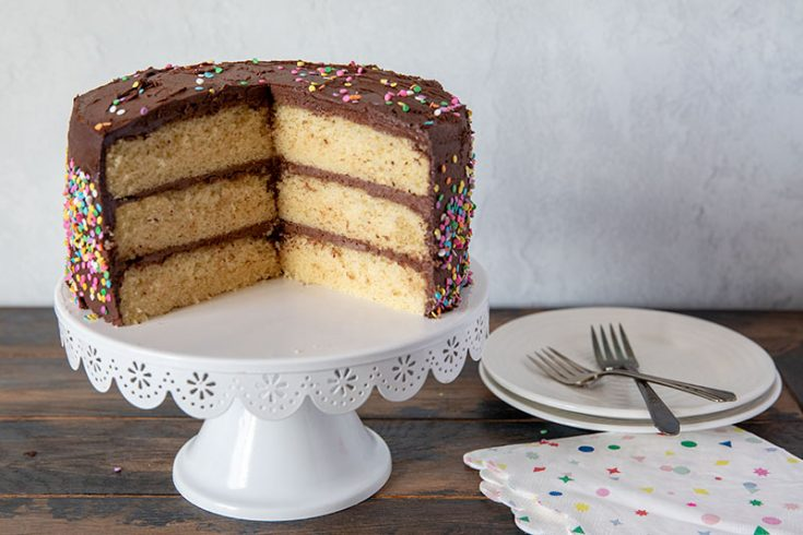 Three-Layer-Yellow-Cake-With-Chocolate-Frosting on a cake stand with a large slice removed