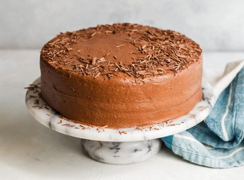 Hershey's Perfectly Chocolate Chocolate Cake Decorated With Shave Chocolate on a decorative cake stand
