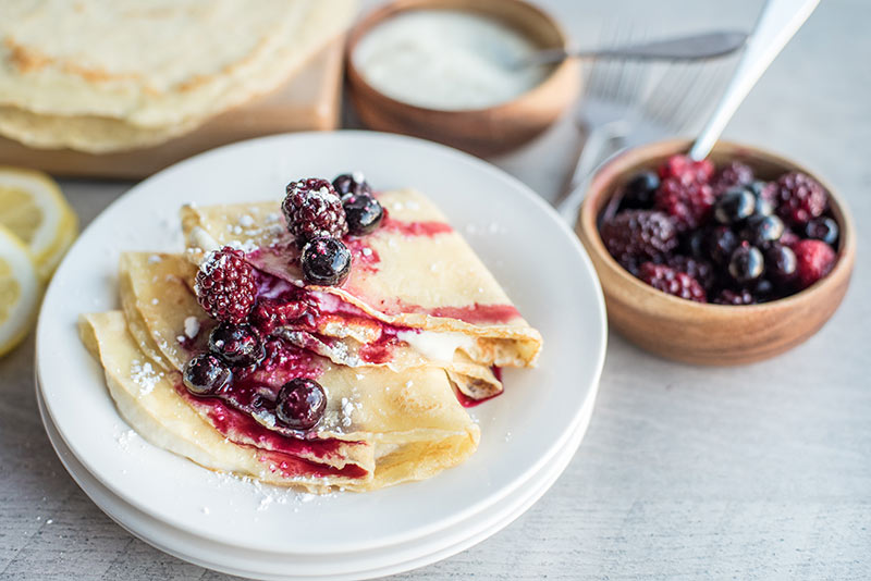 Lemon ricotta crepes plated with fresh berry compote