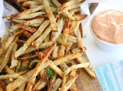 Air fryer french fries sitting next to a cup of dipping sauce