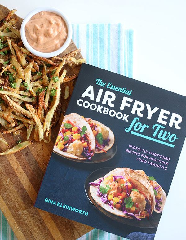 Overhead photo of Garlic Parmesan Air Fryer French Fries sitting next to The Essential Air Fryer Cookbook for Two