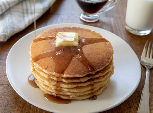 Pancakes with a dollop of butter and maple syrup served on a white plate