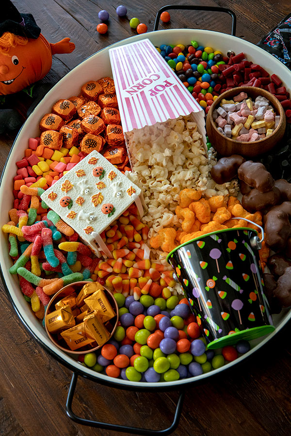 Fun Halloween Movie Board with Caramel M&M\'s in fun Halloween colors, Dove Milk Chocolate Pumpkins; candies, Reese\'s Peanut Butter Bats, Hershey\'s Nuggets,Trolli Sour Worms, Skittles, Starburst, and SweetTart Skulls and Bones.