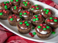 A close up of a plate of Marshmallow Surprise Brownie Bites with red and green mini M&Ms