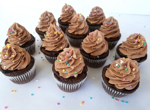 Nutella Frosting swirled on top of chocolate cupcakes with colorful sprinkles