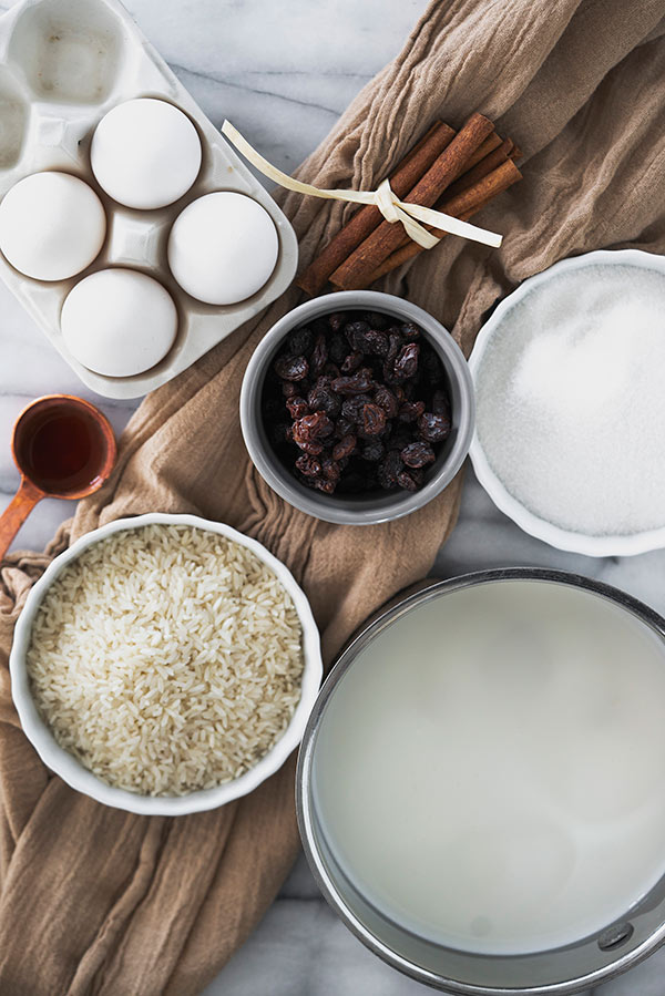 Overhead of ingredients for Old-fashioned rice pudding: eggs, raisins, long-grain white rice, vanilla extract, milk, sugar and cinnamon on a white marble background with a brown linen.