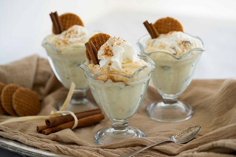 Side view of three ice cream cups filled with homemade old-fashioned rice pudding topped with cinnamon, whipped cream and waffle cookies on a brown linen cloth with cinnamon sticks and more cookies.
