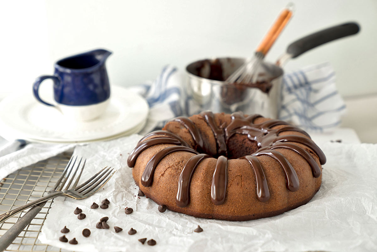 Healthier Chocolate Pound Cake From A Mix on parchment with the pan used to make the glaze in the background.