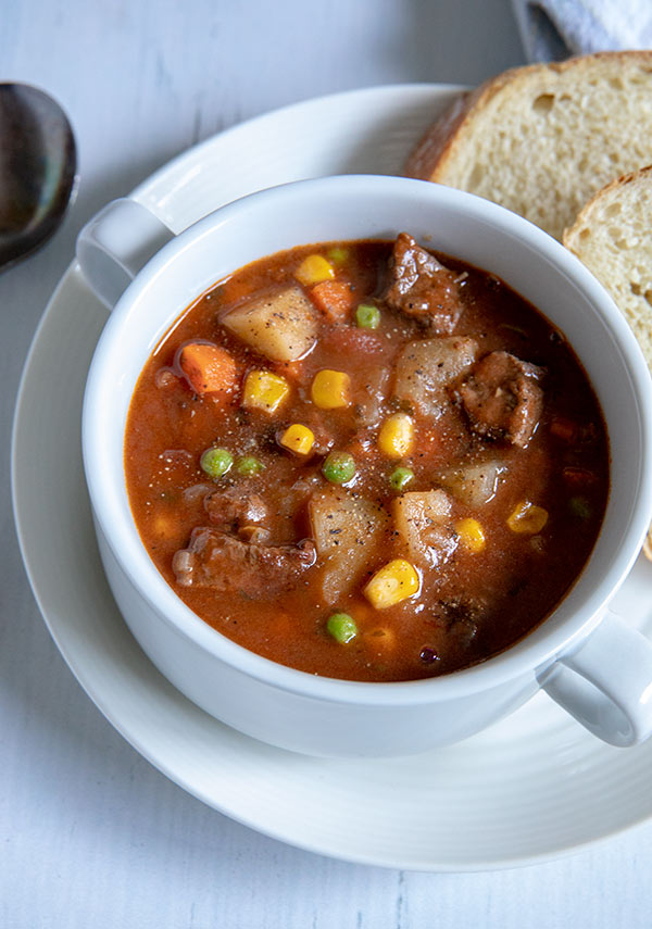 A bowl of round steak beef stew with sliced bread