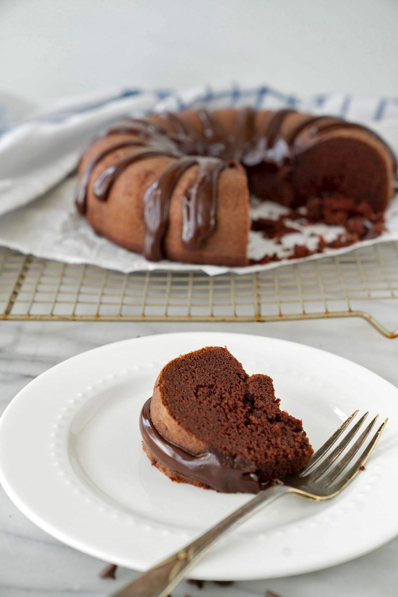 A slice of chocolate bundt cake with drizzle of chocolate frosting on a plate with cake in the background