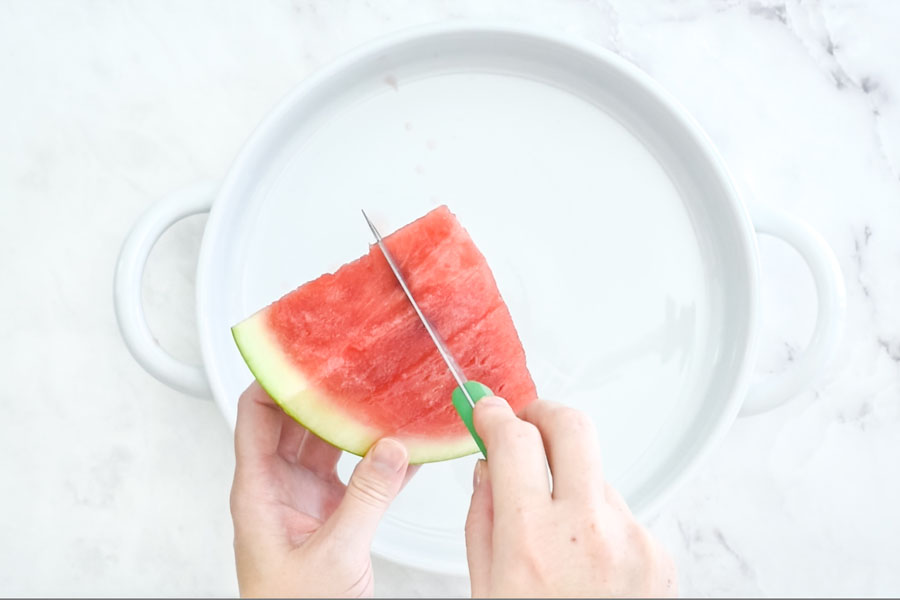 a slice of watermelon being cut into cubes by holding a triangel by the rind and slicing vertically