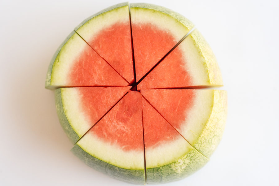 a watermelon on a cutting board sliced into thick wedges with the rind