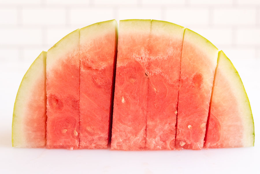 one half of a red watermelon on a cutting board flseh side down sliced into equal triangles before cutting into cubes