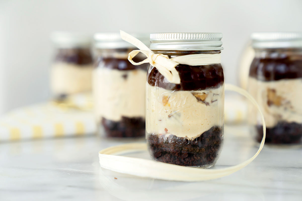 Several Mason jars with No-bake Peanut Butter Cheesecake in a Jar made with chocolate cake, silky cheesecake and creamy ganache topped with Reese's Peanut Butter Cups
